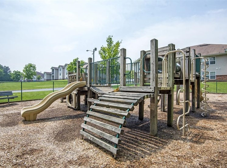 Wooden Playground with Yellow and Green Accents on Mulch with Bench and Fence