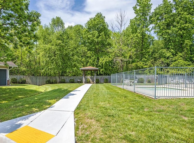 Walkway to Grill and Picnic Area by Swimming  Pool with Treeline in the Background