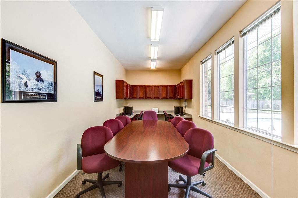 Business Center with Conference Table Maroon Chairs and Computers and Wood Cabinets