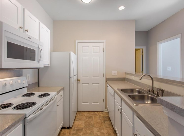 Kitchen with White Cabinets and Appliances with Beige Counters and Breakfast Bar