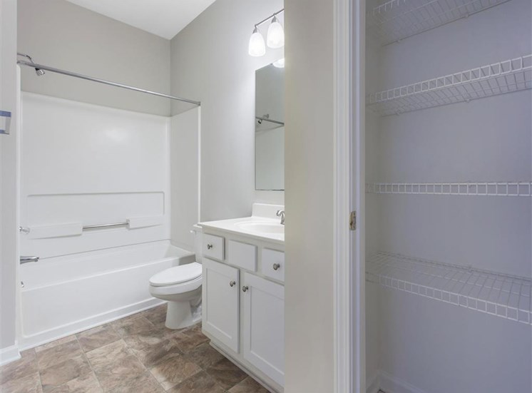 Bathroom with White Cabinets and Counters and Linen Closet with Wire Shelf