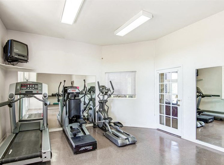 Fitness Center with Exercise Equipment Against Mirrored Wall with Small Mounted TV