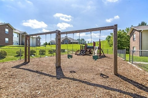Wooden Swing Set with Wooden Playground in the Background