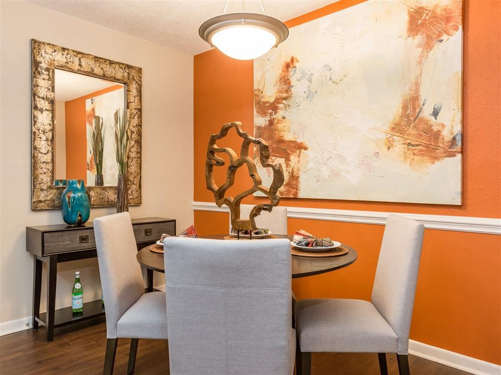 Model Dining Room with Orange Accent Wall Art and Dining Table with Chairs