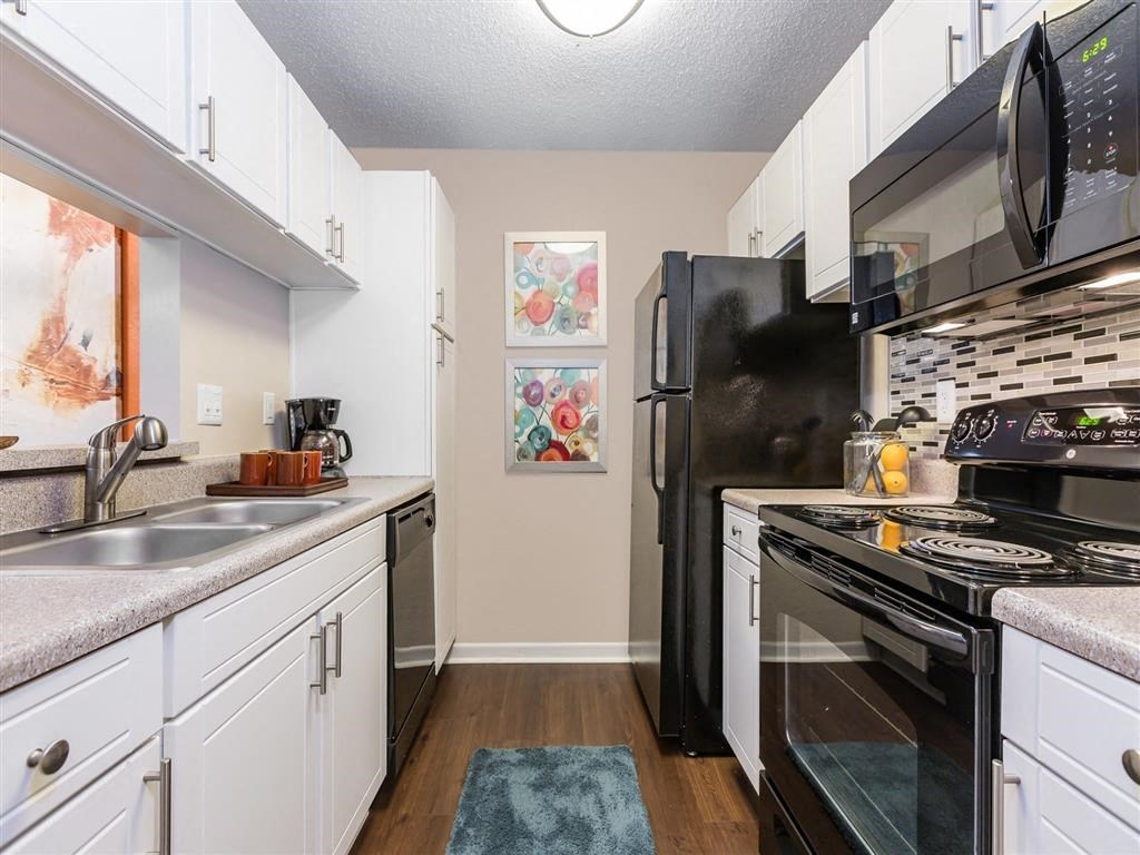 Model Kitchen with White Cabinets Black Appliances Grey Counters with Decorations