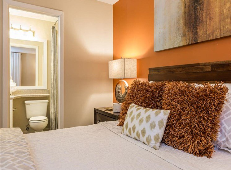 Model Bedroom with Model Bed Orange Accent Wall and En Suite Bathroom