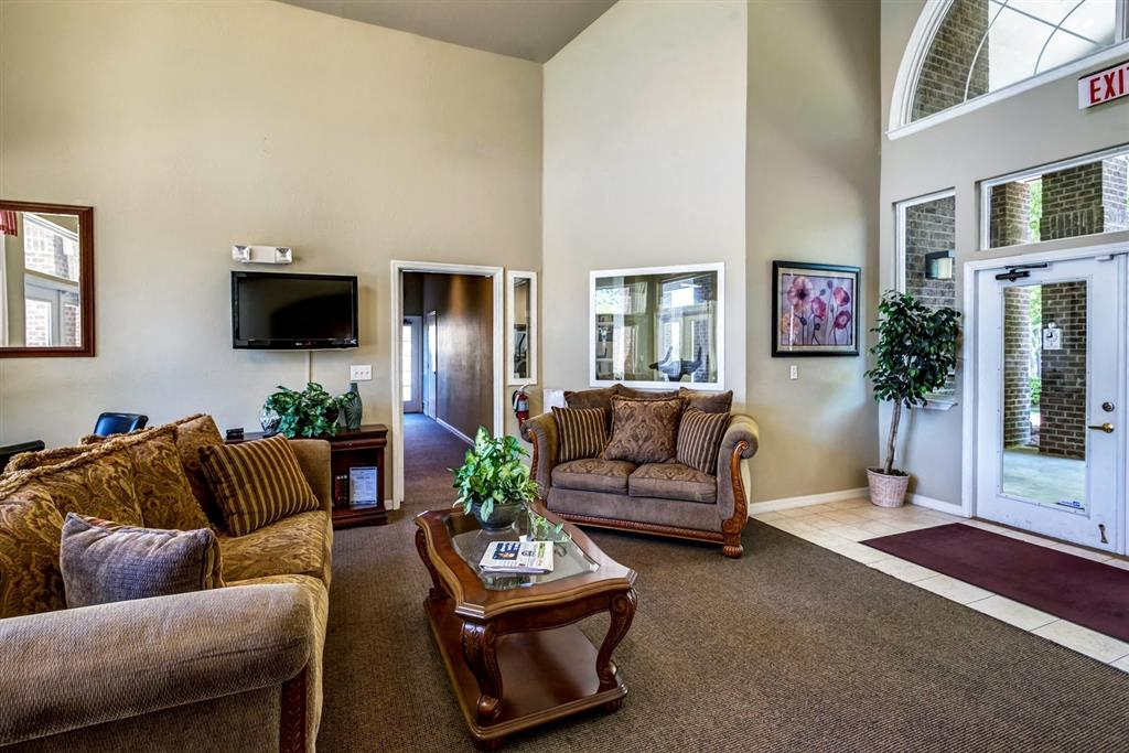 Clubhouse Seating Area with Brown Couches  Coffee Table and Mounted TV