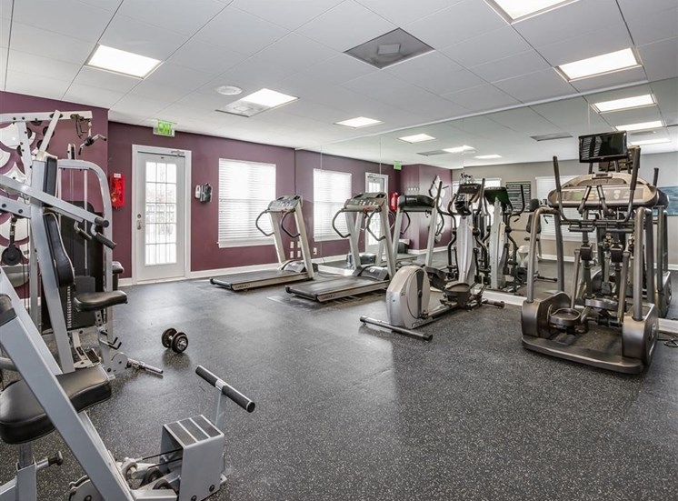 Fitness Center with Exercise Equipment purple Accent Wall and Mirror Accent Wall