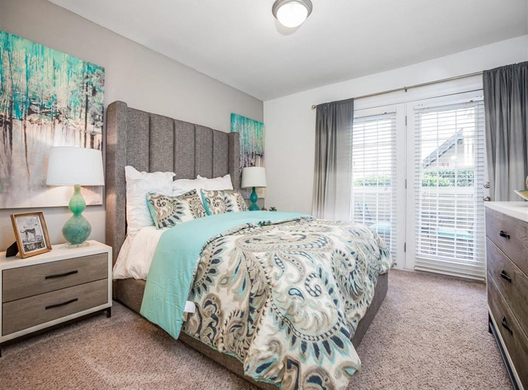 Spacious Model Bedroom with Patio Access and Platform Bed With Large Headboard
