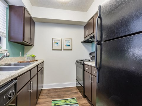 Fully Equipped Kitchen with Brown Cabinets and Black Appliances