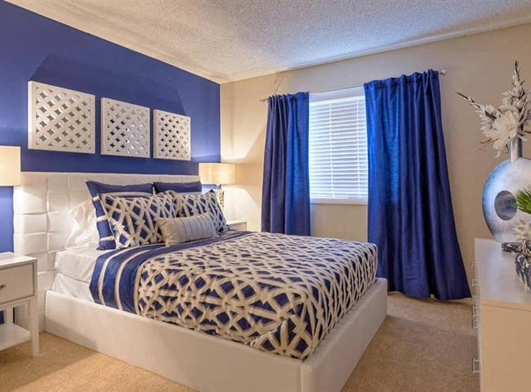 Model Bedroom with Blue Accent Wall White Platform Bed Nightstand and Dresser with Decorations