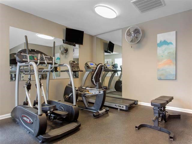 Fitness Center with Exercise Equipment and Mirror Accent Wall Mounted TV and Mounted Fan