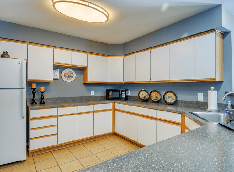 Clubhouse kitchen with tile flooring, white cabinets, and breakfast bar