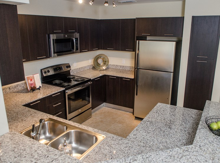 Kitchen with granite style countertops, silver appliances, brown cabinets and tile flooring