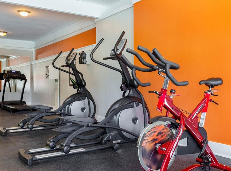 Bright Fitness Center with Exercise Equipment and Orange Accent Wall