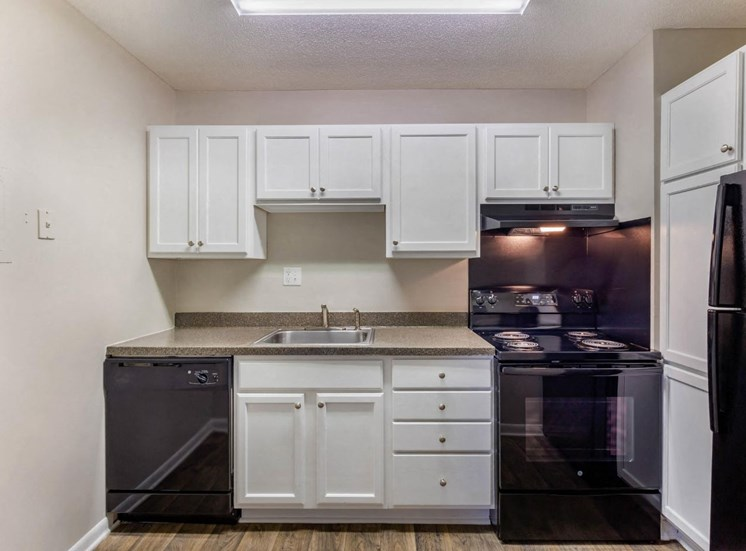 Fully Equipped Kitchen with White Cabinets Grey Counters and Black Appliances