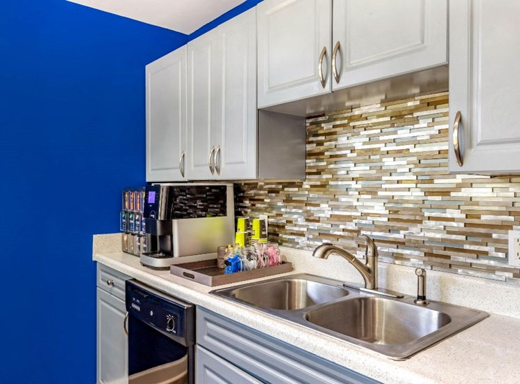 Clubhouse Kitchen with Blue Accent Wall and White Cabinets