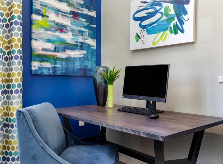 Computer Desk with Padded Chair Next to Blue Accent Wall