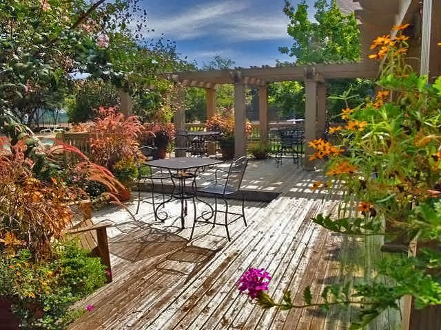 Outdoor courtyard with green landscaping, wood panel flooring, and orange flowers surrounding a table and chairs