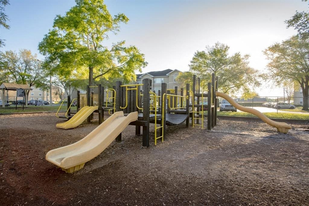 Wood Playground with Yellow Equipment on Mulch with Trees in the Background