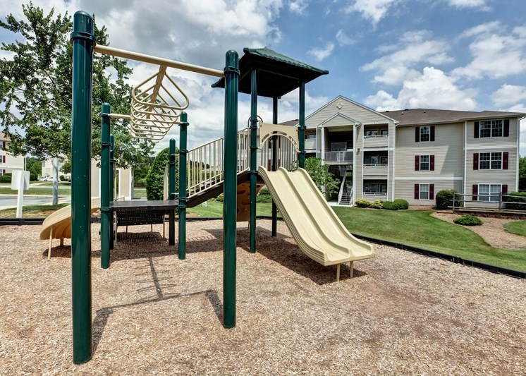 Yellow and green playground with monkey bars and apartment building exterior in the background