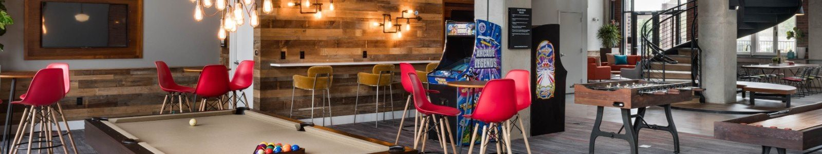 Clubhouse with Billiards Table Arcade Game With Red Bar Stools Shuffleboard Table and Foosball Table