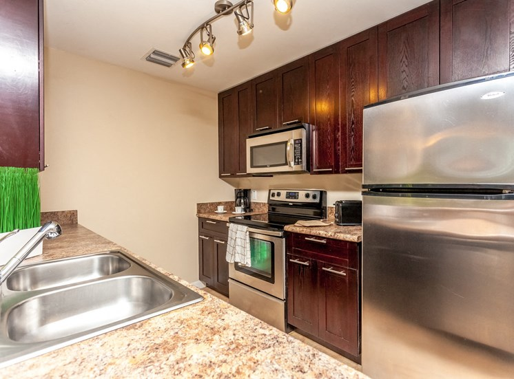 Kitchen with Stainless Steel Appliances, Tan Counters, Wood Cabinets and Decorations