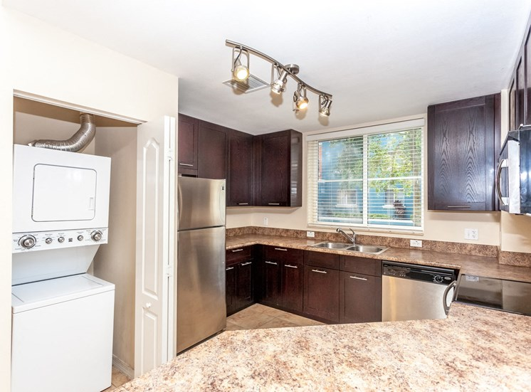 Large kitchen image with stack washer and dryer , stainless steel appliances, tan counters and wood cabinets