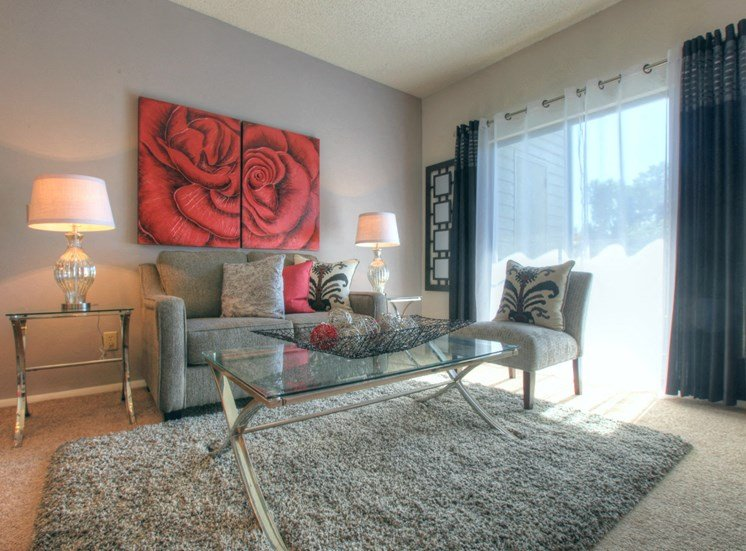 Model Living Room with Grey Shag Rug Gray Couch Glass Coffee Table  and Side Tables with Lamps Next to Sliding Glass Door