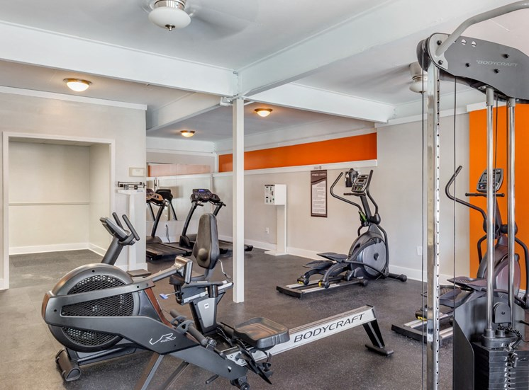 Bright Fitness Center with Exercise Equipment and Mirrored Wall and Orange Accent Wall