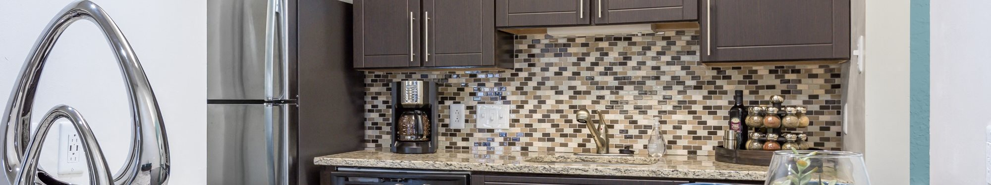 Kitchen with chrome finished appliances, a metal decorative art piece on the bar along with three blue mugs, and wooden cabinetry with a mosaic back splash