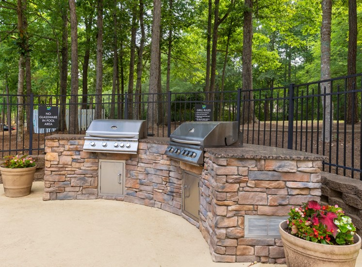Grilling Station with 2 Gas Grills Built Into Stone Outdoor ISland in Front of Fence with Treeline in the Background