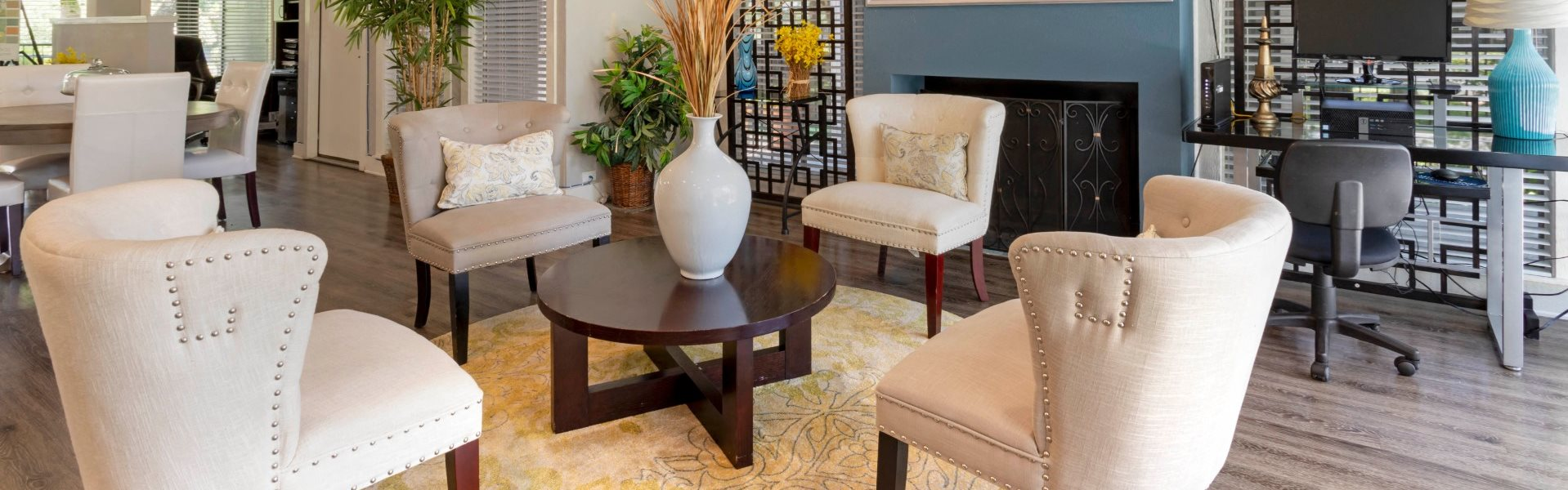 Clubhouse seating Area with 4 White Chairs Surrounding Wooden Coffee Table in Front of Fireplace with Mirror Mounted Next to Computer Desk with Rolling Chair