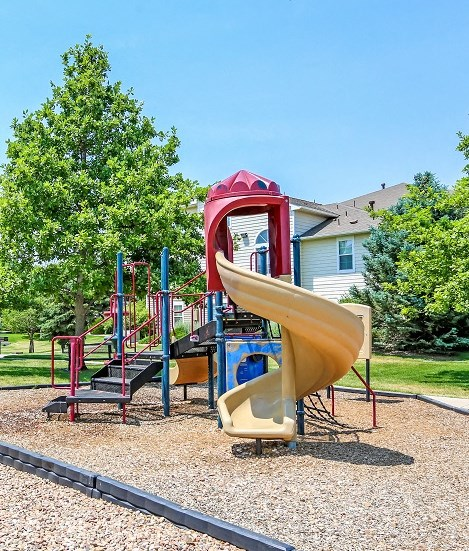 Playground on Mulch in Grassy Courtyard with Building Exterior in the Background