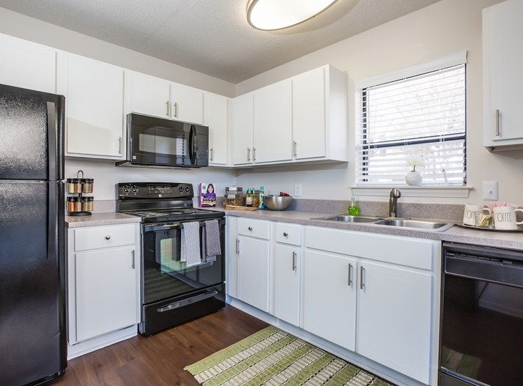 Kitchen with hardwood style flooring, black appliances, and double basin sink