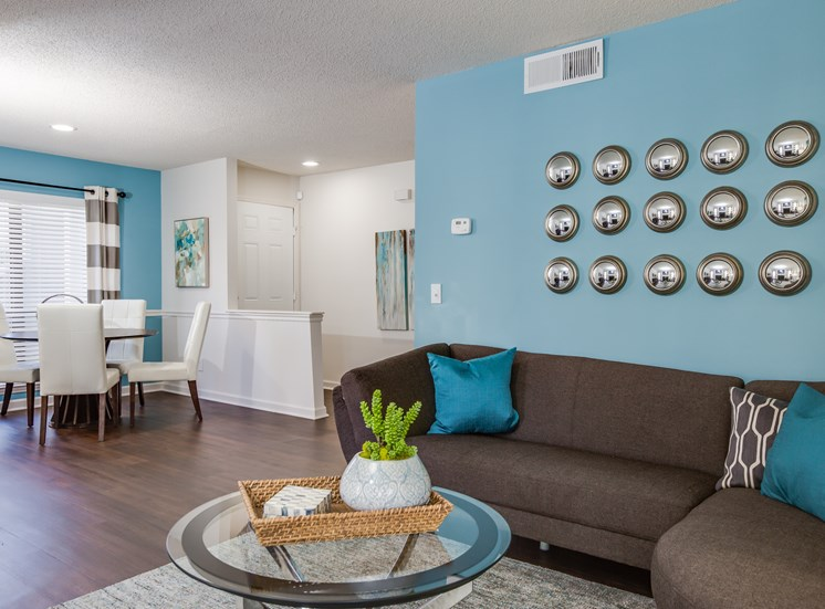 Living room with teal accent walls, decorations on the wall, brown L shaped couch, and hardwood style flooring