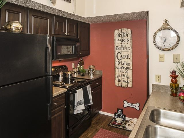 Model Kitchen with Brown Cabinets Black Appliances Tan Counters with Decorations