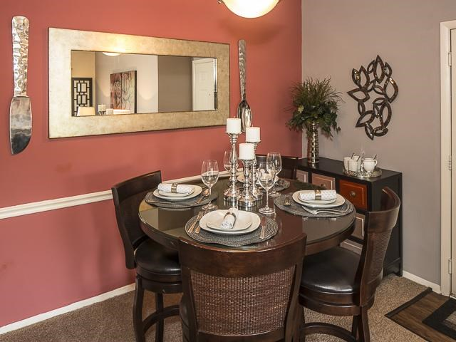 Dining Room with Dining Table Next to Red Wall with Mirror Mounted