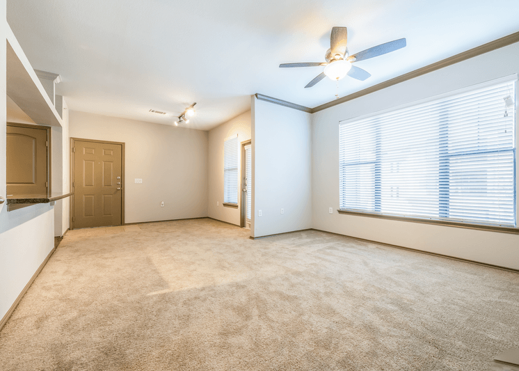 Carpeted living room with large windows and ceiling fan