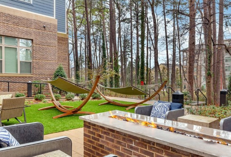 Green Space with Hammocks Next to Seating Area with Firepit with Treeline in the Background