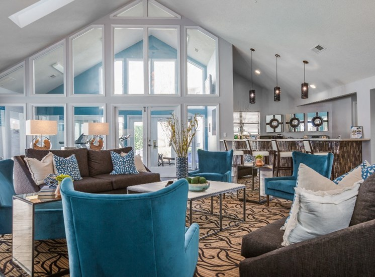 Clubhouse Seating Area with Blue Armchairs and Coffee Table on Area Rug with Large Windows in the Background