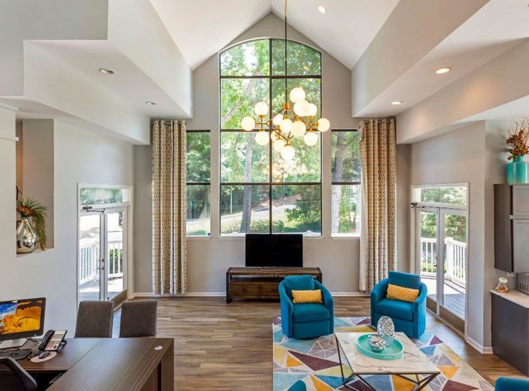 Clubhouse Seating Area with Blue Color Scheme 4 Arm Chairs Surrounding Contemporary Coffee Table with Large Window in the Background