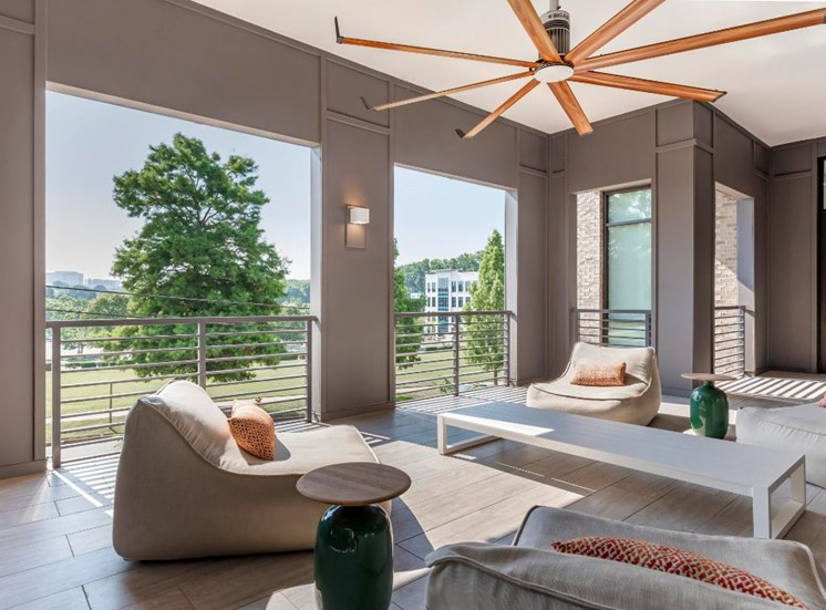Patio seating with sofas over sized ceiling fans and large windows