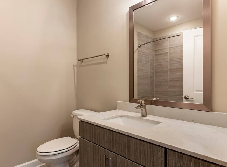 Bathroom with vanity mirror, wooden cabinetry, and towel rack