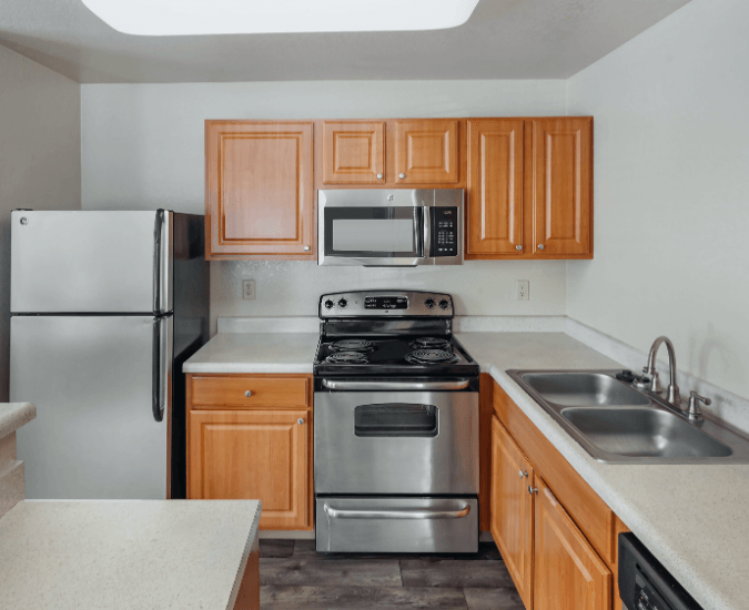 Fully equipped kitchen with stainless steel appliances, double basin sink, and tile flooring