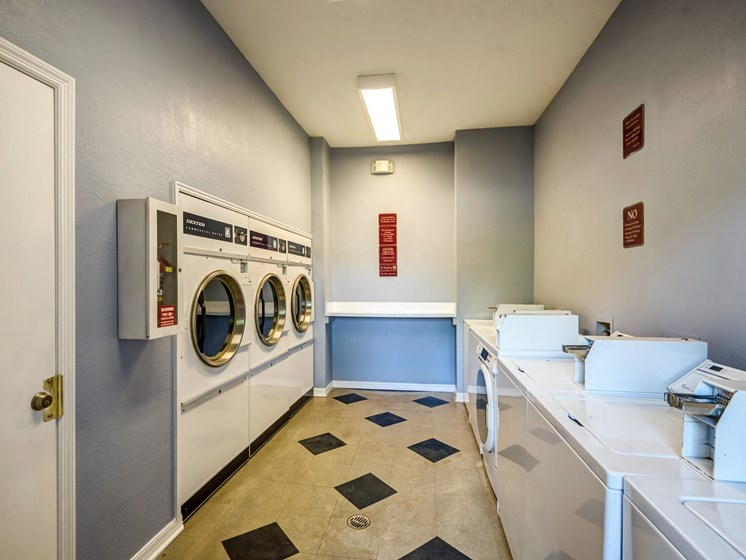 Laundry room with washer and dryers blue walls and tiled floors