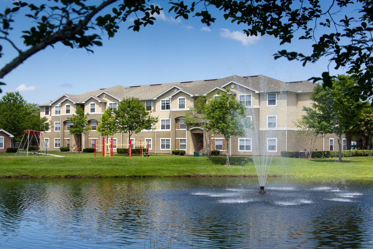 Apartment building exterior surrounded by native landscaping overlooking lake with water fountain feature