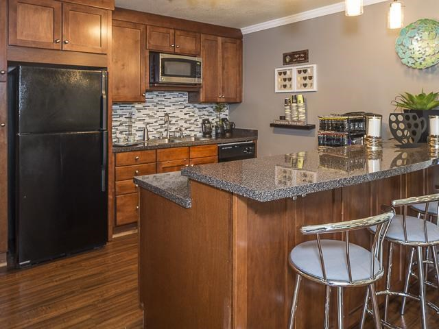 Clubhouse Kitchen with Breakfast Bar Brown Cabinets and Black Appliances