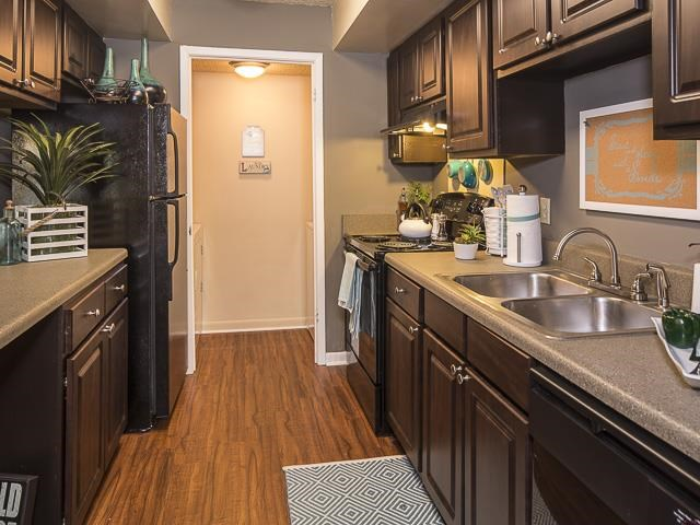 Model Kitchen with Brown Cabinets Black Appliances Grey Counters with Decorations