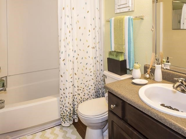 Model Bathroom with White Shower Curtain Brown Cabinets and Tan Counters